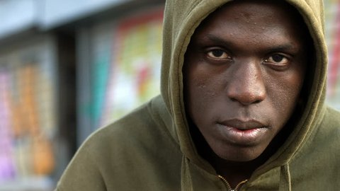 close up on Serious young immigrant African staring at camera