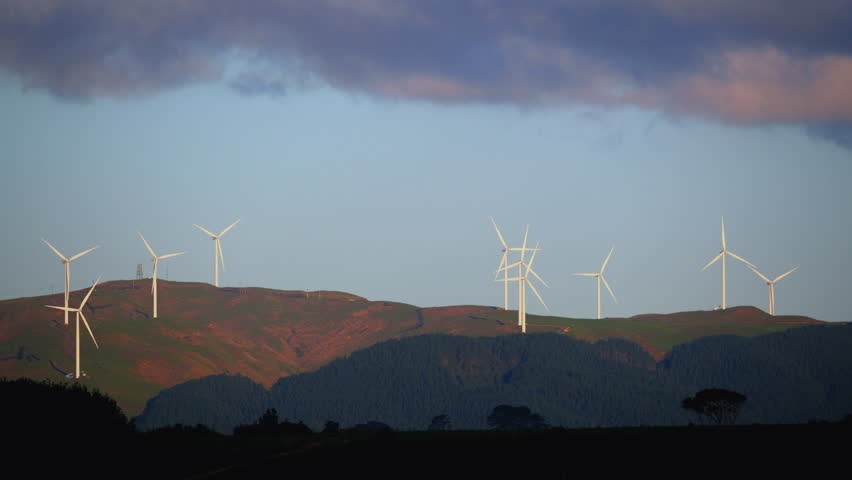 Large wind powered turbines spinning on landscape of hills at dusk or dawn