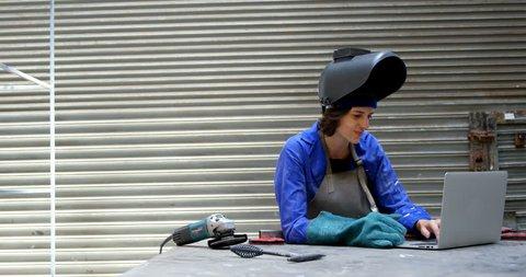 Young female welder using laptop in workshop 4k
