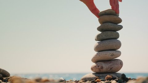 Build a tower of pebbles against the background of the sea. Equilibrium and meditation concept