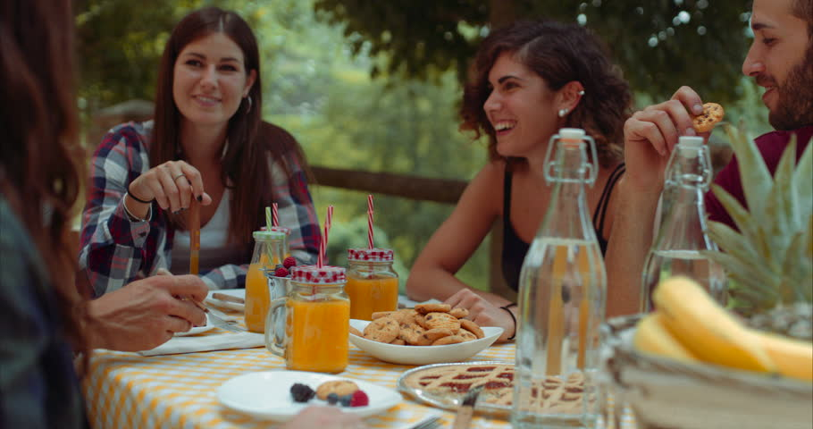 group of friends doing breakfast outdoors in a traditional countryside. shot in slow motion