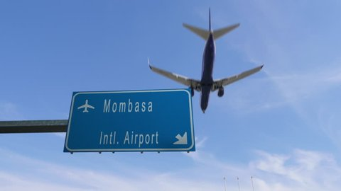 mombasa airport sign airplane passing overhead