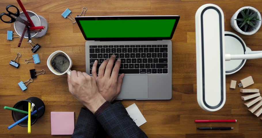 Businessman Working on his Computer, Drinking Coffee. Office Stationery Supplies around the Computer. Top view Hands using Laptop with Green Screen. Closing the Computer. Work Well Done.