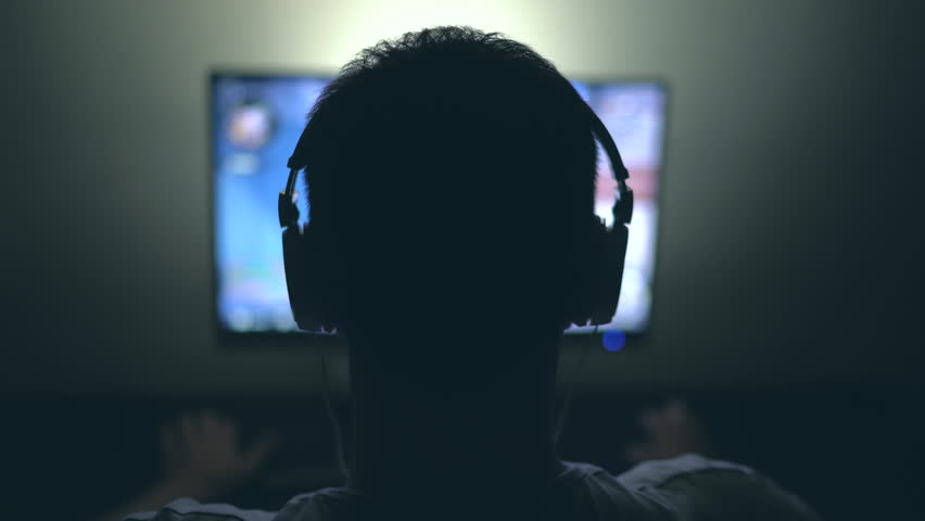 Gamer with Headphones in Dark Room playing Video Game at Night