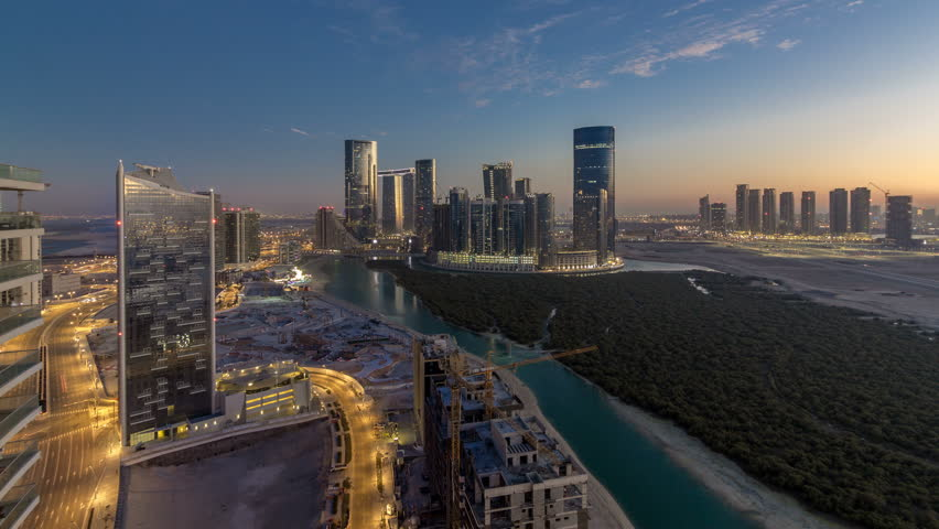 Skyscrapers on Al Reem and Al Maryah Island in Abu Dhabi day to night transition timelapse after sunset from above. Aerial citiscape from Al Reem Island with illuminated buildings