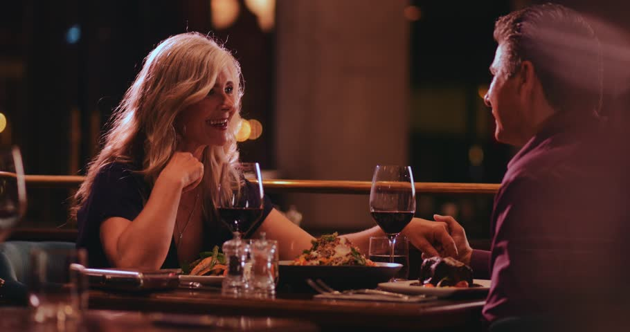 Mature couple holding hands, flirting and having fun on dinner date night at gourmet restaurant