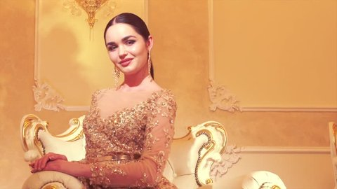 Beauty gorgeous woman in beautiful evening dress posing in victorian style interior room. Luxurious style. Beautiful model girl in golden wedding dress. Slow motion. 4K UHD video 3840X2160