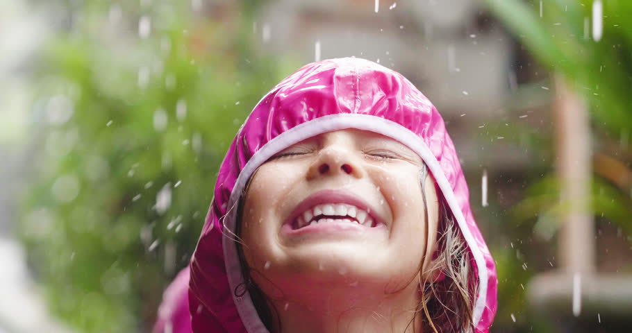 A happy girl is playing in the rain and is happy because she has fun. He opens his arms as a sign of freedom and love for nature.  | Shutterstock HD Video #1013246024