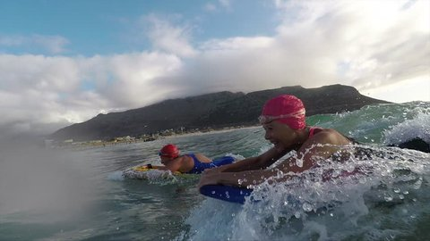 Senior women body boarding together at the beach