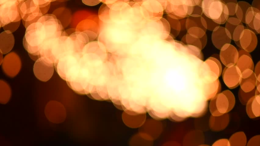 Holiday Blurred abstract motion background, bokeh. Gold color bokeh defocused circles blur. Falling circle lights on dark backdrop. Fireworks. Slow Motion 4K UHD video