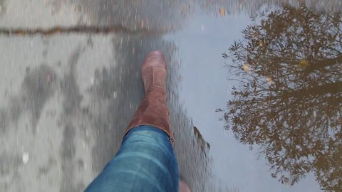 Point of view shot of female legs isolated on grey wet from rain pavement covered with golden fall leaves. Adult woman in brown leather boots walks outdoors in autumn nasty rainy day.