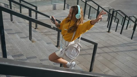 Portrait of young cute attractive young girl in urban city streets background listening to music with headphones. Woman wearing yellow blouse and silver skirt.