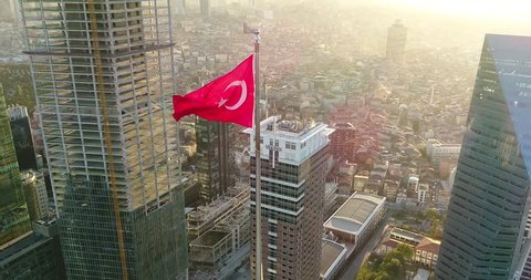 Turkish flag swinging in the middle of the financial city at sunset