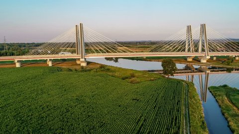 New modern double cable-stayed bridge over Vistula River in Krakow, Poland, and its reflection in water at sunset. Part of the ring road around Krakow. Aerial flyby video