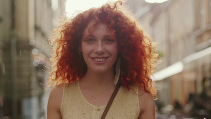 Young smiling attractive woman with red curly hair walking in the rain on the street look at camera spinning happy cute fashion water silhouette summer face female lonely stop close up | Shutterstock HD Video #1013312204