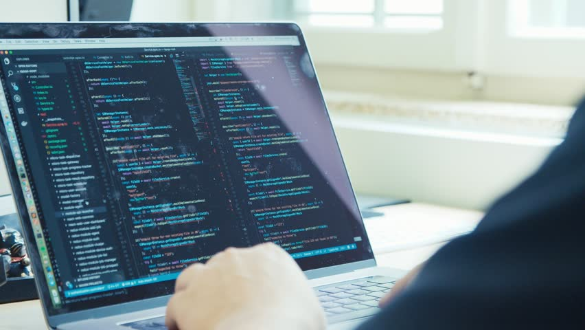 Computer programmer sitting in front of a screen coding software | Shutterstock HD Video #1013315984
