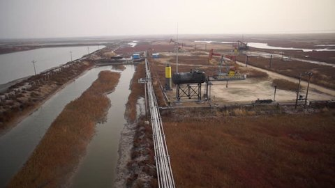 Aerial view, following a  worker on his bike in wetland and red beach landscape with oil pump, oil well, pipeline and petroleum factory in Panjin, Liaoning, China