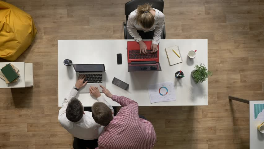 Two business men talking over laptop when woman working and sitting at table in modern office, topshot, work concept #1013336264