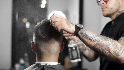 Barber wets hair by spray and combs them, tattoed barber makes haircut for customer at the barber shop, man's haircut and shaving at the hairdresser, barber shop and shaving salon