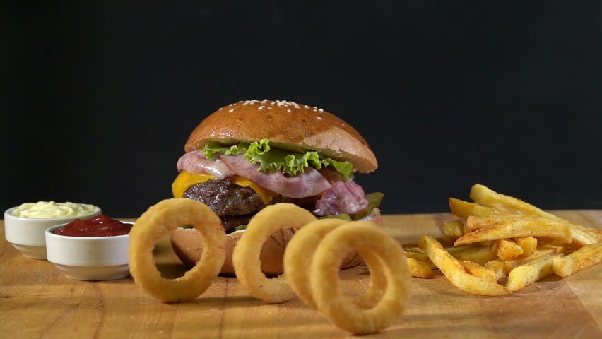 Crispy onion rings come to the hamburger and patatos. mayonnaise and ketchup - Slow motion 240 fps