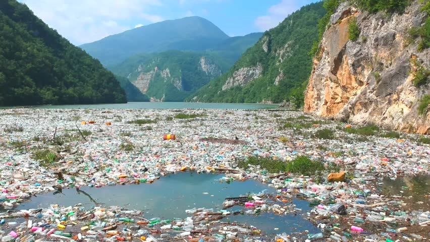Plastic bottles in a polluted river water. Aerial view, drone view | Shutterstock HD Video #1013359634