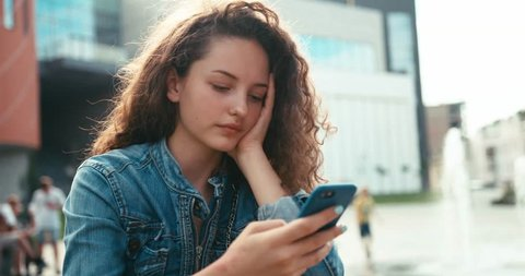 Portrait of the beautiful cheerful girl with braces and curly dark hair chatting, texting and browsing on the mobile phone. 4k.