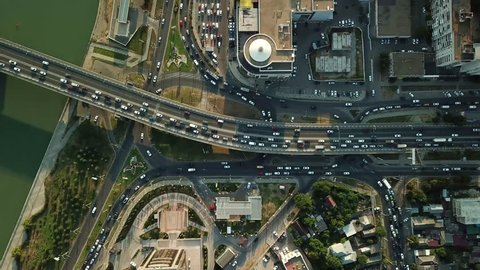 Aerial Drone Flight View of freeway busy city rush hour heavy traffic jam highway, .  Aerial view of the vehicular intersection,  traffic at peak hour with cars on the road and on the bridge.
