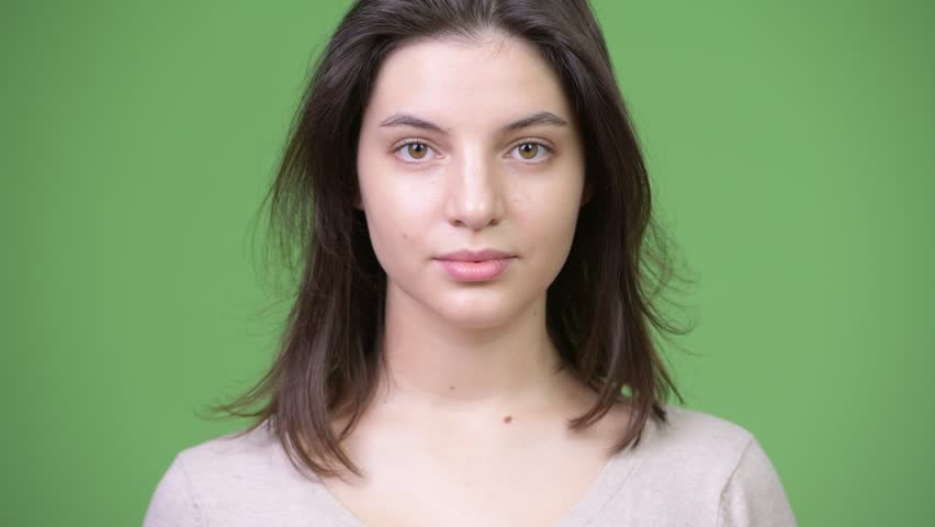Young beautiful woman against green background | Shutterstock HD Video #1013377184