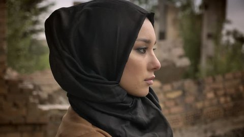 Young muslim woman in hijab looking away and at camera, worried and afraid, ruined building in background