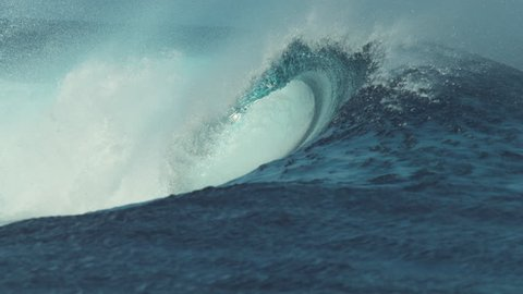 SLOW MOTION, CLOSE UP: Beautiful deep blue tube wave in the wild Pacific Ocean curls towards a remote island on a sunny day in summer. Spectacular shot of wild barrel wave coming from the exotic sea.