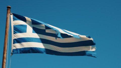 The Greek flag dances in the wind -- in slow motion, in beautiful Santorini, Greece.