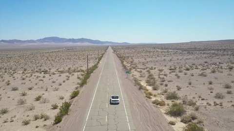 Driving on a lonesome road in the middle of nowhere, aerial view