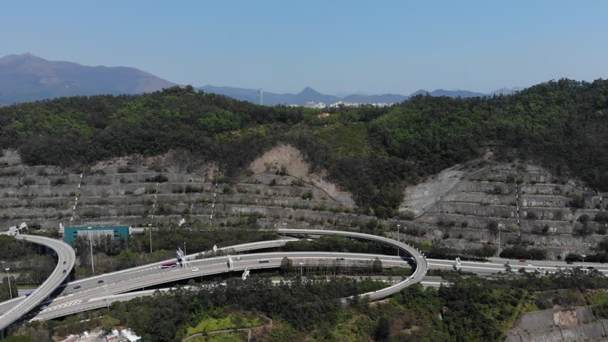 Large cut of mountain for roads interchange, aerial shot of transportation network at mountainous area. Camera move forward. Green trees on top of hill, side reinforcement with steps seen ahead