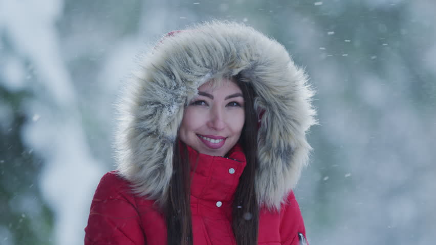 Smiling woman wearing a winter jacket with fur hood.