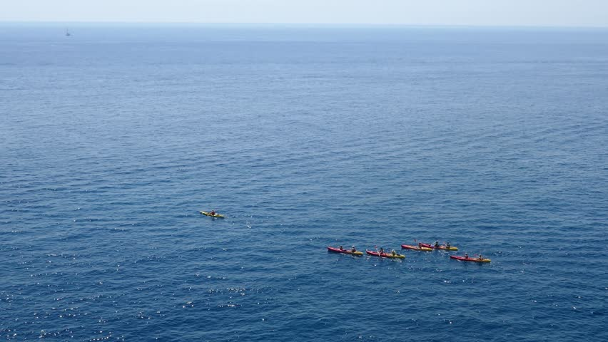 Long shot aerial footage of a group of sea kayakers following their leader in the open sea