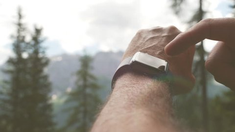 Slow motion close up of hiker man using a smart watch in a mountain trail at sunset or sunset for healthy exercises. Sport and technology.