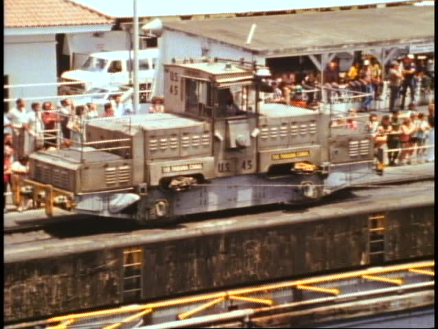QUEEN ELIZABETH 2, 1982, QE2 World Cruise, a mule pulls ship in the Panama Canal