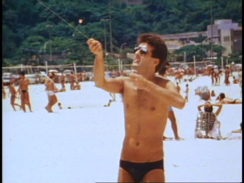 BRAZIL, 1982, Rio de Janeiro, Copacabana beach, close up, young man fling kite