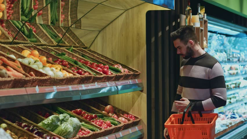 Shot of a handsome young man looking thoughtfully at the supermarket shelves choosing vegetables copyspace buying shopping consumerism customer buyer thinking retail sales people | Shutterstock HD Video #1013491424