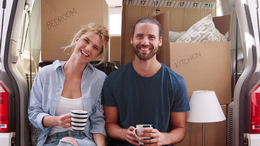 Portrait Of Couple Taking A Break In Back Of Removal Truck On Moving Day | Shutterstock HD Video #1013516084