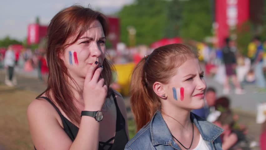 Two female fans cheer for French team while football match. Front view   Shutterstock HD Video #1013519894