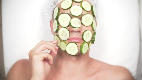 Strange man with face pack. A young man does cosmetic procedures for the face of a house in front of a mirror. 4k, cucumber mask