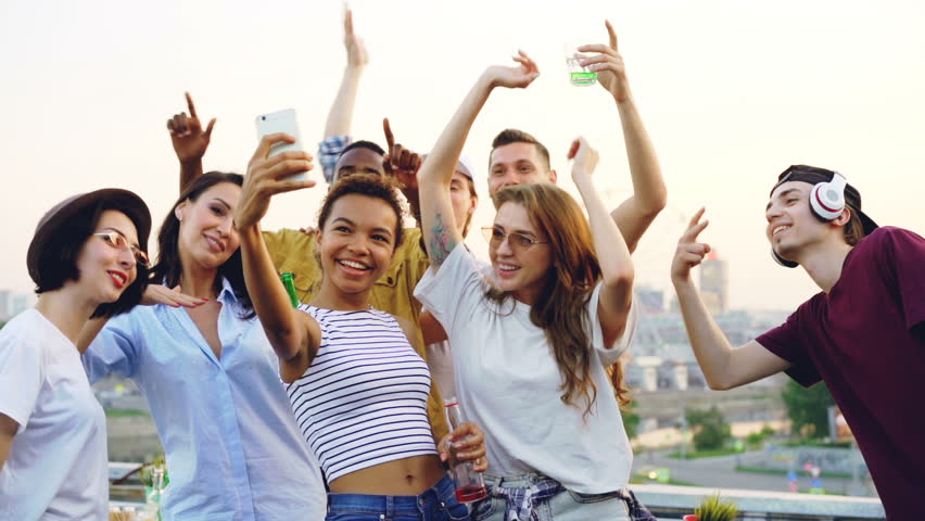 Slow motion of attractive African American girl taking selfie at outdoor party with her friends dancing and posing for camera. Entertainment, youth and technology concept. | Shutterstock HD Video #1013525384