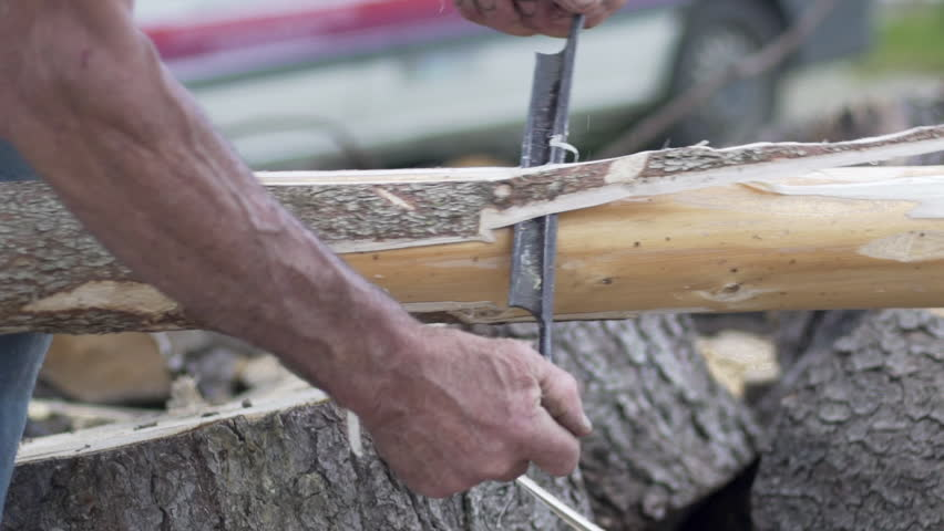 Lumberjack woodsman debarking the bark of a tree in the mountains. Worker and work concept. | Shutterstock HD Video #1013530484