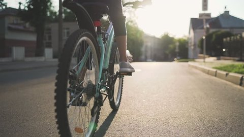 Girl Kid Riding Bike in Summer in City at Beautiful Sunset  in Slow Motion