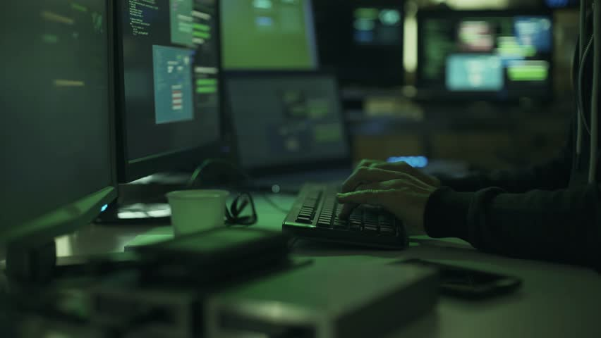 Black hat hacker working in the dark with his computers, he is stealing data and hacking networks, cyber crime concept | Shutterstock HD Video #1013568914