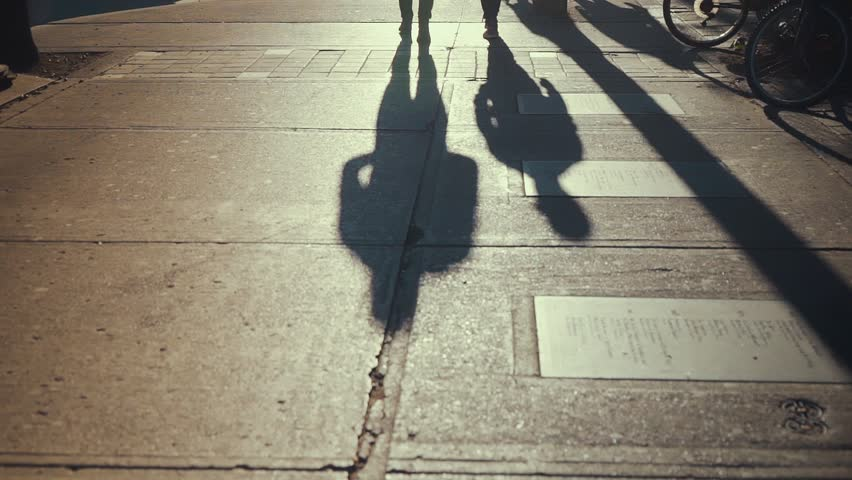 The evening sun casts shadows of two people walking down Queen Street West in Toronto SLOW MOTION | Shutterstock HD Video #1013574644