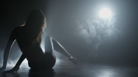 Silhouette of elegant young woman performing contemporary dance on floor in dark studio filled with fog
