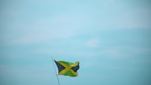 Jamaica Flag in a Blue Sky. Waving the flag of Jamaica against the sky