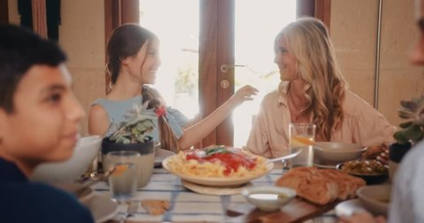 Happy grandmother and teenage granddaughter having fun and hugging during family lunch at home
